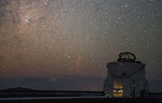 """这张照片中捕捉到的""""红色精灵"""",是在高海拔地区、出现在雷暴上空的一种罕见自然现象。图片的前景中,ESO甚大望远镜的一部分、一个1.8米辅助望远镜孤独地伫立在夜空之下。(图片来源:P. Horálek/ESO)"""
