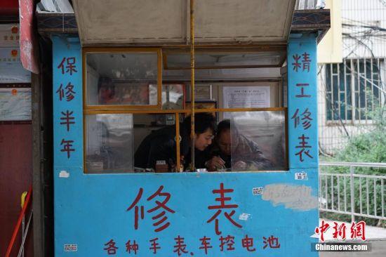 """1月11日,在贵州省贵阳市,一家经营了35年的修表店照常营业。随着计时产品的多样化,挂钟和手表用得越来越少,曾经在街头巷尾常见的钟表修理匠也日渐消失。然而这家老修表店仍然经营依旧。这家""""刘文昆修表店""""是一间不足4平米的简易小店铺,68岁的刘文昆从事修表行当已有35年的时间,是附近一带小有名气的修表匠,经过他的手,让无数已经停产,无法更换零件的老钟表""""起死回生"""",然而他的这一门手艺却没有师承,完全是自学积累起来的。如今,刘文昆的儿子刘庭辉也在跟着他学习钟表修理手艺,让父业子承。图为刘文昆的小店。中新社记者 李婧 摄"""