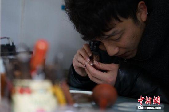 """1月11日,在贵州省贵阳市,一家经营了35年的修表店照常营业。随着计时产品的多样化,挂钟和手表用得越来越少,曾经在街头巷尾常见的钟表修理匠也日渐消失。然而这家老修表店仍然经营依旧。这家""""刘文昆修表店""""是一间不足4平米的简易小店铺,68岁的刘文昆从事修表行当已有35年的时间,是附近一带小有名气的修表匠,经过他的手,让无数已经停产,无法更换零件的老钟表""""起死回生"""",然而他的这一门手艺却没有师承,完全是自学积累起来的。如今,刘文昆的儿子刘庭辉也在跟着他学习钟表修理手艺,让父业子承。图为刘庭辉学习修表技术。中新社记者 李婧 摄"""