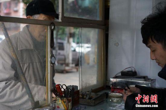 """1月11日,在贵州省贵阳市,一家经营了35年的修表店照常营业。随着计时产品的多样化,挂钟和手表用得越来越少,曾经在街头巷尾常见的钟表修理匠也日渐消失。然而这家老修表店仍然经营依旧。这家""""刘文昆修表店""""是一间不足4平米的简易小店铺,68岁的刘文昆从事修表行当已有35年的时间,是附近一带小有名气的修表匠,经过他的手,让无数已经停产,无法更换零件的老钟表""""起死回生"""",然而他的这一门手艺却没有师承,完全是自学积累起来的。如今,刘文昆的儿子刘庭辉也在跟着他学习钟表修理手艺,让父业子承。图为刘庭辉接待前来修表的顾客。中新社记者 李婧 摄"""