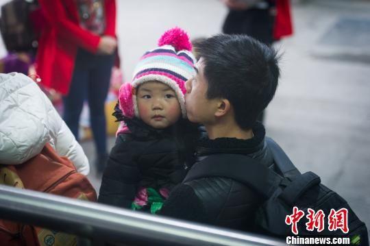 1月21日,贵阳北站,一位旅客怀抱小孩在候车。贺俊怡 摄