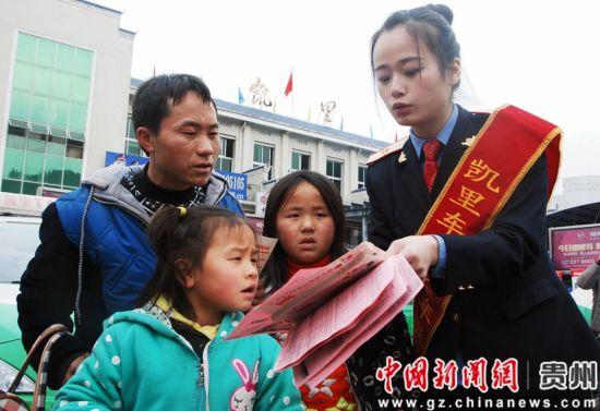 """图为成都铁路局贵州境内六盘水站""""橘色精灵""""志愿者为旅客提供咨询服务。"""