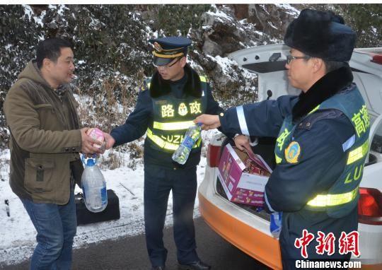 图为路政人员为滞留人员发放方便面及饮用水。贵州省水城高速公路管理处供图