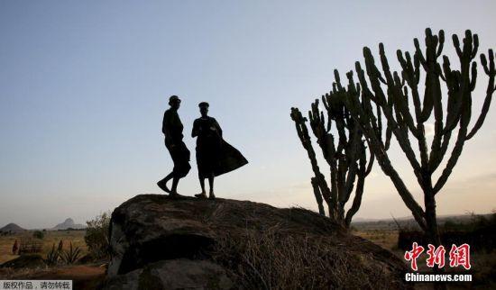 当地时间2月17日,乌干达东北山区的卡拉莫贾,两名原始部落的男子站在一处高地上。