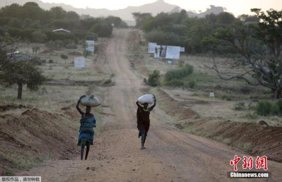乌干达部落的妇女头顶包裹走在路上。