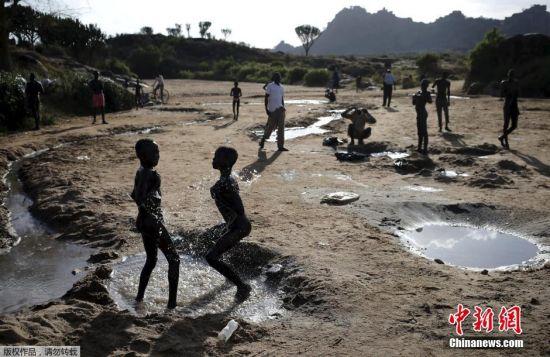 卡拉莫贾的孩子们在一条干涸的河床边洗澡。