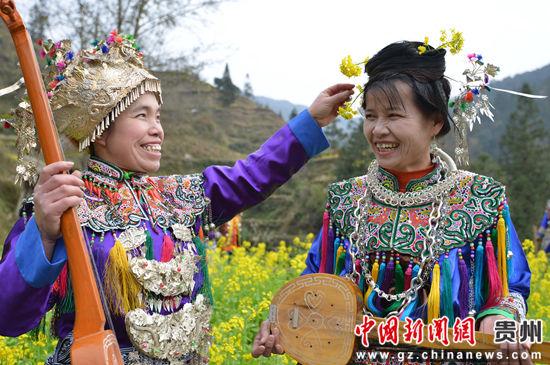 贵州省榕江县寨蒿镇寿洞村侗戏歌队琵琶手互相插花。