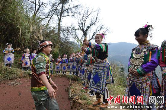 贵州省榕江县寨蒿镇寿洞村侗戏歌队在田边抓鱼。
