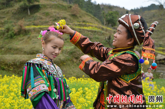 贵州省榕江县寨蒿镇寿洞村一对情侣在插花。
