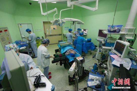 3月5日,31岁的麻醉医生阙媛媛8时20分进入手术室,开始一天繁忙的工作。图为交班结束后,阙媛媛进入手术间开始对即将要手术的病人进行病人信息核对,开启麻醉机、氧源,检查麻醉机运行是否正常,以及各种麻醉药品及急救药品的准备,一切准备妥当后,病人被送进手术室。核对病人信息和手术部位方式无误后,她开始通过给病人进行麻醉诱导,顺利插入气管导管,保证病人呼吸道通畅、麻醉深度足够后,手术医生开始为病人做手术。中新社记者 贺俊怡 摄