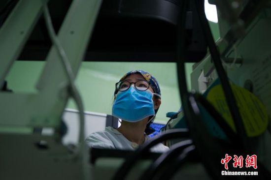 3月5日,31岁的麻醉医生阙媛媛8时20分进入手术室,开始一天繁忙的工作。图为手术医生开始为病人做手术,而阙媛媛则退到一边,双眼紧紧盯着麻醉机上的监测仪,严密地观察病人的生命体征并进行麻醉文书的记录,同时还要不时地注意手术台上手术进行的情况。中新社记者 贺俊怡 摄