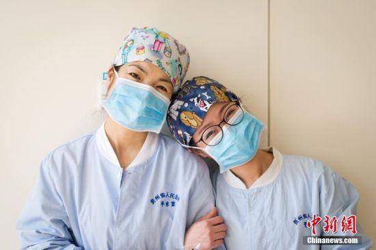 3月5日,31岁的麻醉医生阙媛媛8时20分进入手术室,开始一天繁忙的工作。图为下午时分,窗外阳光和煦,阙媛媛利用难得的休息时间,与护士长在手术室的走廊上合影。从研究生毕业参加工作到至今,阙媛媛从事手术麻醉工作7年,由于工作的特殊性,她与同事相处的时间比和家人相处的时间长。中新社记者 贺俊怡 摄