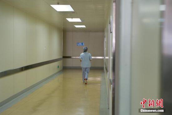 3月5日,31岁的麻醉医生阙媛媛8时20分进入手术室,开始一天繁忙的工作。图为阙媛媛奔忙于她所负责的三个手术室之间。阙媛媛介绍,给病人打麻醉并非难事,密切监测手术中病人的生命体征及维持生命体征的稳定才是麻醉医生最重要的职责。中新社记者 贺俊怡 摄