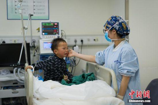 3月5日,31岁的麻醉医生阙媛媛8时20分进入手术室,开始一天繁忙的工作。图为阙媛媛在观察病人生命体征。由于是周六,麻醉后恢复室的人手不够,阙媛媛必须兼顾多项工作,抬病人下手术台、到麻醉后恢复室观察病人生命体征等。中新社记者 贺俊怡 摄