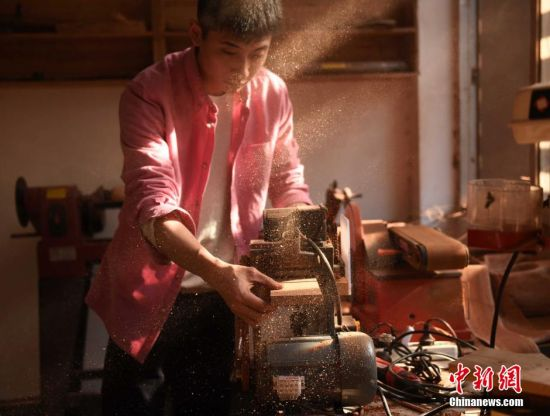 """3月6日,重庆两位大学老师正在工作室里加工制作木头工艺品。崔旭和王玖分别在重庆交通大学和四川美术学院任教。由于双方都对木头有浓厚兴趣,于是决定在全球不同国家寻找不同种类的木头,将寻找到的木头做成一套木头标本库。图为""""木头控""""老师在工作室里打磨木头。 周毅 摄"""