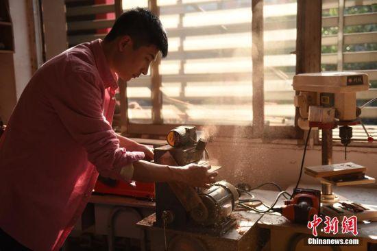 老师在工作室里打磨木头。 周毅 摄