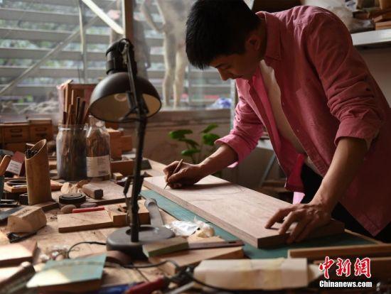 """""""木头控""""老师在工作室里为准备加工的木头工艺品画图。 周毅 摄"""