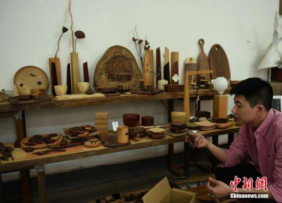 """""""木头控""""老师展示制作的木头工艺品。 周毅 摄"""