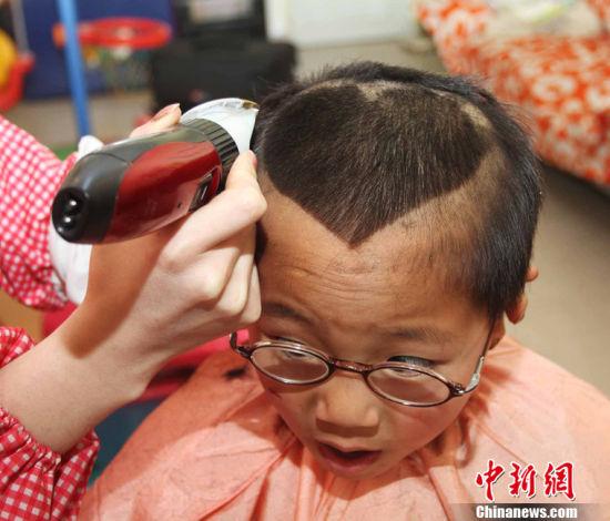 """一个孩子正在""""剃喜头""""。 耿国庆 摄"""