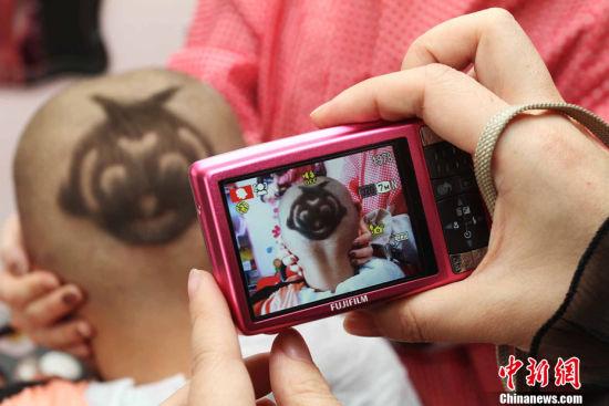 """一位家长用数码相机拍下孩子的孙悟空造型""""喜头""""。耿国庆 摄"""