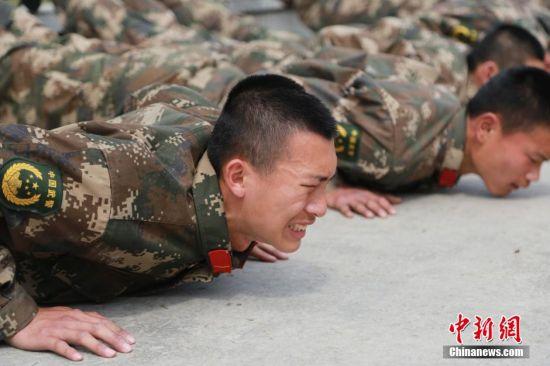 """3月14日,经武警贵州总队黔南支队严格考核,55名新兵55人脱颖而出,成功进入全程淘汰制的魔鬼训练营,将开展为期三个月的""""魔鬼式""""训练。""""海选""""从3月11日开始,武警贵州总队黔南支队对新兵进行武装负重越野、俯卧撑、引体向上等科目的考核,并针对情况反应和抗压力的临场表现等方面进行测试。中新社发 张海涛 摄"""