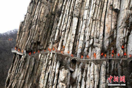 """2016年3月17日,河南登封嵩山少林三皇寨书册崖现绝壁武者,这些只能在金庸武侠小说里才能见到的""""飞檐走壁"""",在现实中真实上演,武者们身穿练功服,在悬崖绝壁上修炼少林功夫。 王中举 摄"""