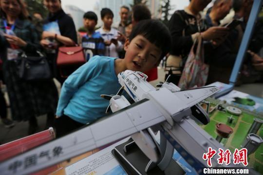 3月20日,贵州省气象局气象日活动。小朋友被3D人影飞机吸引。 石开银 摄