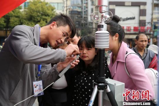 3月20日,贵州省气象局工作人员为市民介绍气象仪器。 张蕾 摄