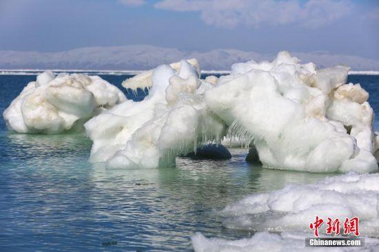 """3月24日,青海湖湖面上的""""冰桥""""。青海湖开湖分为""""文开""""和""""武开"""",2016年青海湖开湖属""""文开""""。""""文开""""是指封冻一冬的青海湖随周边气温升高,缓慢融化,而""""武开""""则为在猛烈季风下,湖面冰层破裂被相互挤压着推向岸边。气象资料显示2016年青海湖开始解冻日期较去年推迟27天,较历年开湖日期平均(2003~2015年)提前了8天。 中新社记者 罗云鹏 摄"""