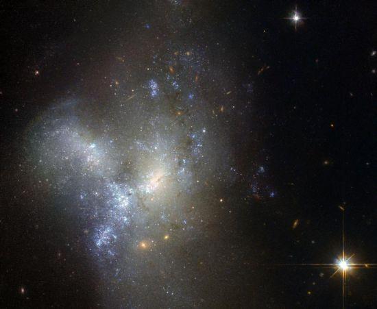 在这张由哈勃太空望远镜捕捉的图片中,显示的是星系合并的过程。在距离我们约3000万光年的NGC 1487星系,两个或者两个以上的星系融合在了一起,形成了一个新的星系。(图片来源: 美国宇航局官网)