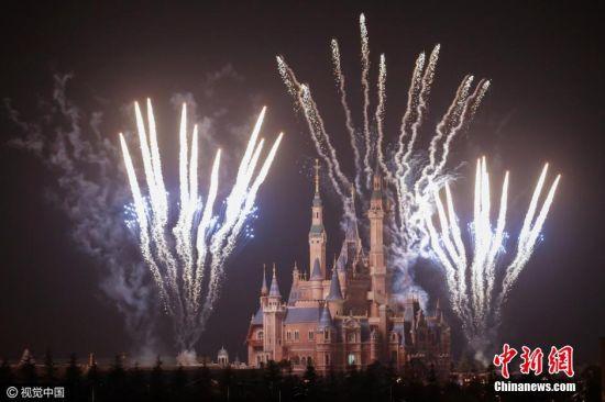 """2016年3月28日晚,上海迪士尼乐园进行了第一次烟花试放。晚上9时许,两道明亮的烟火在人们的欢呼中划破天际。在随后的27分钟内,10余组姿态各异的烟火在空中依次绽放,万千烟花""""喷薄""""而出,迪士尼城堡在烟火的照射下清晰可见。图片来源:视觉中国"""