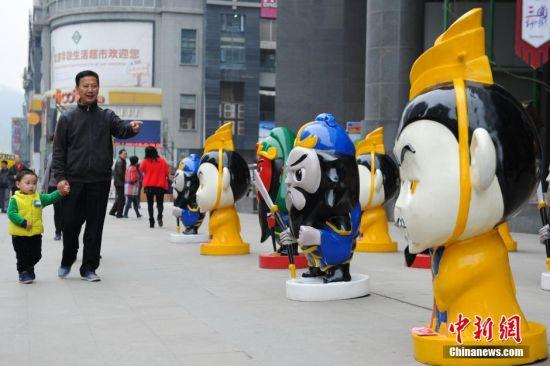 4月1日,贵州省遵义市一商场外,商家摆上刘备、关羽、张飞等三国卡通人物造型,引民众关注。图为一位老者为小朋友讲述三国故事。 中新社记者 贺俊怡 摄