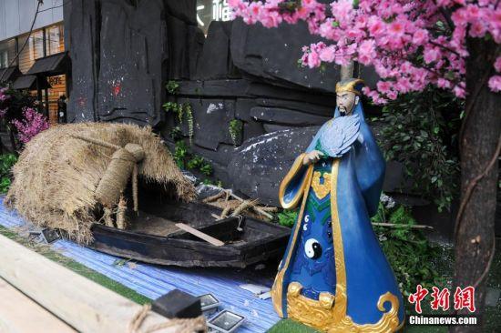 4月1日,贵州省遵义市一商场外,商家摆上刘备、关羽、张飞等三国卡通人物造型,引民众关注。图为诸葛亮草船借箭造型。 中新社记者 贺俊怡 摄