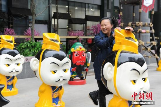4月1日,贵州省遵义市一商场外,商家摆上刘备、关羽、张飞等三国卡通人物造型,引民众关注。图为一市民与刘备卡通人物造型合影。 中新社记者 贺俊怡 摄