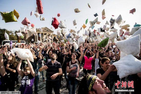 """4月2日是国际""""枕头大战""""日。在这一天,多个国家的""""枕头大战""""爱好者相约走上街头,用独特的方式来庆祝他们的节日。如今,""""枕头大战""""成为许多人缓解紧张生活节奏和释放压力的一种有趣的发泄方式。图为匈牙利民众进行枕头大战。"""