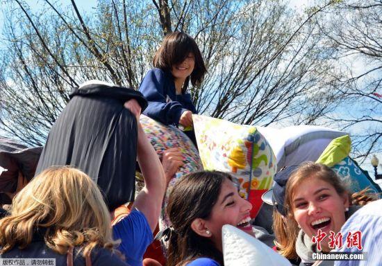 """4月2日是国际""""枕头大战""""日。在这一天,多个国家的""""枕头大战""""爱好者相约走上街头,用独特的方式来庆祝他们的节日。如今,""""枕头大战""""成为许多人缓解紧张生活节奏和释放压力的一种有趣的发泄方式。图为美国华盛顿民众进行枕头大战。"""