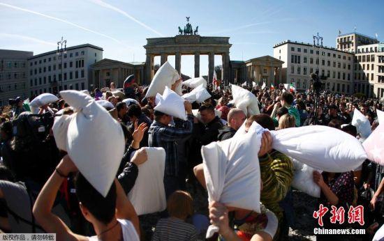 """4月2日是国际""""枕头大战""""日。在这一天,多个国家的""""枕头大战""""爱好者相约走上街头,用独特的方式来庆祝他们的节日。如今,""""枕头大战""""成为许多人缓解紧张生活节奏和释放压力的一种有趣的发泄方式。图为德国柏林民众进行枕头大战。"""