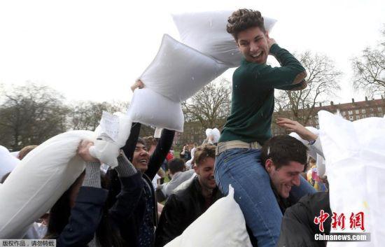 """4月2日是国际""""枕头大战""""日。在这一天,多个国家的""""枕头大战""""爱好者相约走上街头,用独特的方式来庆祝他们的节日。如今,""""枕头大战""""成为许多人缓解紧张生活节奏和释放压力的一种有趣的发泄方式。图为英国伦敦民众进行枕头大战。"""