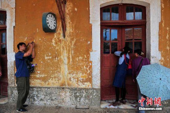 4月3日,游客在拍摄火车站的标志物三面钟的子钟。清明小长假期间,云南蒙自市碧色寨火车站独特的法式建筑风格,吸引众多游客到此游览。滇越铁路于1910年建成,碧色寨火车站成为这条铁路的核心枢纽,是中国最古老的火车站之一。 中新社记者 刘冉阳 摄