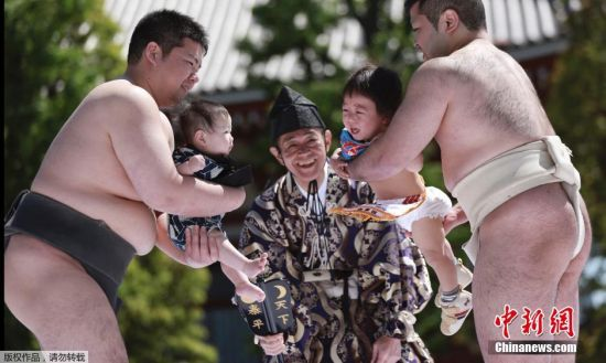 """当地时间4月29日,日本东京,相扑选手抱着小孩参加""""宝宝哭相扑""""比赛。日本人相信如果相扑手能使自己的宝宝嚎啕大哭,那么孩子便能健康成长。"""