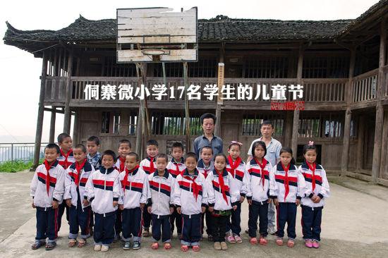 6月1日,正值国际六一儿童节,高赧小学17名学生身着校服与老师在教学楼前合影。贵州省榕江县寨蒿镇高赧小学,自2013年并校以来,由于高赧侗寨离中心小学比较远,一年级、二年级年幼的学生没办法到中心学校寄宿就读,当地教育部门为了照顾年幼的孩子,在村里保留了两个年级,配备了2名教师。校长杨正谊已在这所小学当了17年的老师,有36年教龄的吴顺标则是因为并校后才到高赧小学任教,目前他们共同承担这所只有17名学生的微型小学的全部课程。 中新社记者 贺俊怡 摄