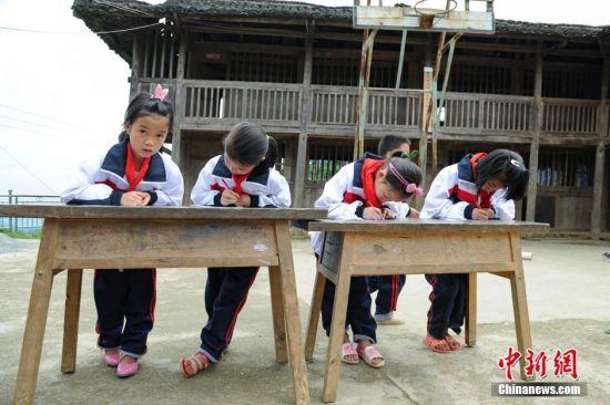 6月1日,一年级4名女同学在进行古诗词默写比赛。当日,贵州省榕江县高赧小学,一年级、二年级17个孩子,过一个与平时一样的儿童节。榕江县寨蒿镇高赧小学,自2013年并校以来,由于高赧侗寨离中心小学比较远,一年级、二年级年幼的学生没办法到中心学校寄宿就读,当地教育部门为了照顾年幼的孩子,在村里保留了两个年级,配备了2名教师。校长杨正谊已在这所小学当了17年的老师,有36年教龄的吴顺标则是因为并校后才到高赧小学任教,目前他们共同承担这所只有17名学生的微型小学的全部课程。 中新社记者 贺俊怡 摄