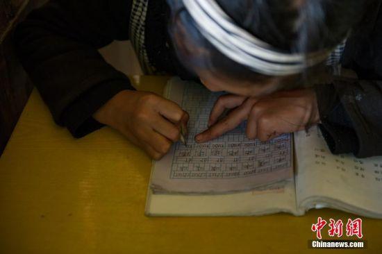 5月30日,一年级学生杨紫云在教室里写作业,她今年8岁,手中的铅笔用到很短也舍不得扔掉。贵州省榕江县寨蒿镇高赧小学,自2013年并校以来,由于高赧侗寨离中心小学比较远,一年级、二年级年幼的学生没办法到中心学校寄宿就读,当地教育部门为了照顾年幼的孩子,在村里保留了两个年级,配备了2名教师。校长杨正谊已在这所小学当了17年的老师,有36年教龄的吴顺标则是因为并校后才到高赧小学任教,目前他们共同承担这所只有17名学生的微型小学的全部课程。 中新社记者 贺俊怡 摄