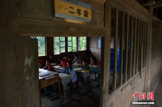 二年级8名同学在吊脚楼里上课,这栋侗族吊脚楼校舍,建于1996年,至今已使用了20年。贵州省榕江县寨蒿镇高赧小学,自2013年并校以来,由于高赧侗寨离中心小学比较远,一年级、二年级年幼的学生没办法到中心学校寄宿就读,当地教育部门为了照顾年幼的孩子,在村里保留了两个年级,配备了2名教师。校长杨正谊已在这所小学当了17年的老师,有36年教龄的吴顺标则是因为并校后才到高赧小学任教,目前他们共同承担这所只有17名学生的微型小学的全部课程。 中新社记者 贺俊怡 摄