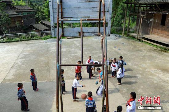 6月1日,孩子们在破旧的篮球架下,进行拍球比赛。当日,贵州省榕江县高赧小学,一年级、二年级17个孩子,过一个与平时一样的儿童节。榕江县寨蒿镇高赧小学,自2013年并校以来,由于高赧侗寨离中心小学比较远,一年级、二年级年幼的学生没办法到中心学校寄宿就读,当地教育部门为了照顾年幼的孩子,在村里保留了两个年级,配备了2名教师。校长杨正谊已在这所小学当了17年的老师,有36年教龄的吴顺标则是因为并校后才到高赧小学任教,目前他们共同承担这所只有17名学生的微型小学的全部课程。 中新社记者 贺俊怡 摄