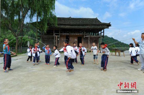 6月1日,孩子们在校长杨正谊的带领下,集体跳绳庆祝六一儿童节。当日,贵州省榕江县高赧小学,一年级、二年级17个孩子,过一个与平时一样的儿童节。榕江县寨蒿镇高赧小学,自2013年并校以来,由于高赧侗寨离中心小学比较远,一年级、二年级年幼的学生没办法到中心学校寄宿就读,当地教育部门为了照顾年幼的孩子,在村里保留了两个年级,配备了2名教师。校长杨正谊已在这所小学当了17年的老师,有36年教龄的吴顺标则是因为并校后才到高赧小学任教,目前他们共同承担这所只有17名学生的微型小学的全部课程。 中新社记者 贺俊怡 摄