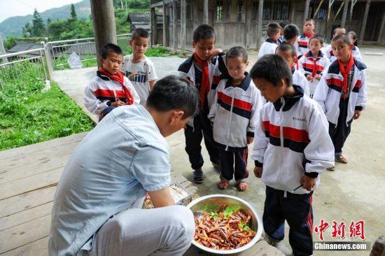 6月1日,校长杨正谊在为孩子准备六一活动的奖品:糖果。当日,贵州省榕江县高赧小学,一年级、二年级17个孩子,过一个与平时一样的儿童节。榕江县寨蒿镇高赧小学,自2013年并校以来,由于高赧侗寨离中心小学比较远,一年级、二年级年幼的学生没办法到中心学校寄宿就读,当地教育部门为了照顾年幼的孩子,在村里保留了两个年级,配备了2名教师。校长杨正谊已在这所小学当了17年的老师,有36年教龄的吴顺标则是因为并校后才到高赧小学任教,目前他们共同承担这所只有17名学生的微型小学的全部课程。 中新社记者 贺俊怡 摄