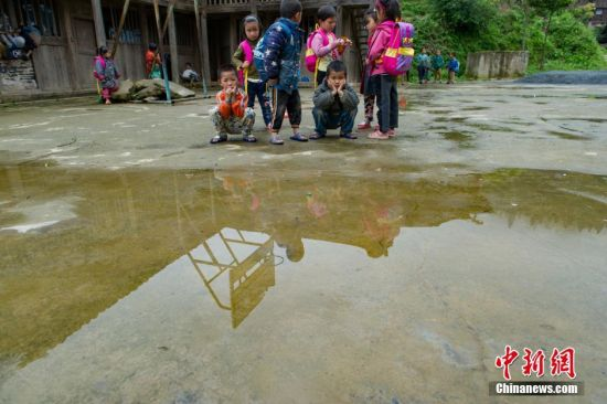 5月30日,雨天里,操场积满水,孩子们在操场上望着水塘发呆。贵州省榕江县寨蒿镇高赧小学,自2013年并校以来,由于高赧侗寨离中心小学比较远,一年级、二年级年幼的学生没办法到中心学校寄宿就读,当地教育部门为了照顾年幼的孩子,在村里保留了两个年级,配备了2名教师。校长杨正谊已在这所小学当了17年的老师,有36年教龄的吴顺标则是因为并校后才到高赧小学任教,目前他们共同承担这所只有17名学生的微型小学的全部课程。 中新社记者 贺俊怡 摄