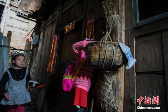 一年级学生杨紫云,8岁,家里有5个姐姐,除了大姐嫁人之外,另外的4个姐姐都在上学。每天放学后,由于正值农忙时节,爸妈把午餐放置在屋外的竹篓里,杨紫云放学后,与同伴杨怡一起帮助家里照顾家禽。贵州省榕江县寨蒿镇高赧小学,自2013年并校以来,由于高赧侗寨离中心小学比较远,一年级、二年级年幼的学生没办法到中心学校寄宿就读,当地教育部门为了照顾年幼的孩子,在村里保留了两个年级,配备了2名教师。校长杨正谊已在这所小学当了17年的老师,有36年教龄的吴顺标则是因为并校后才到高赧小学任教,目前他们共同承担这所只有17名学生的微型小学的全部课程。 中新社记者 贺俊怡 摄