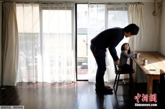 简主义者直树(Naoki Numahata)与他2岁的女儿在家中。